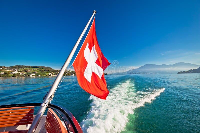 在小船流动的Luzern湖的瑞士旗子 免版税图库摄影