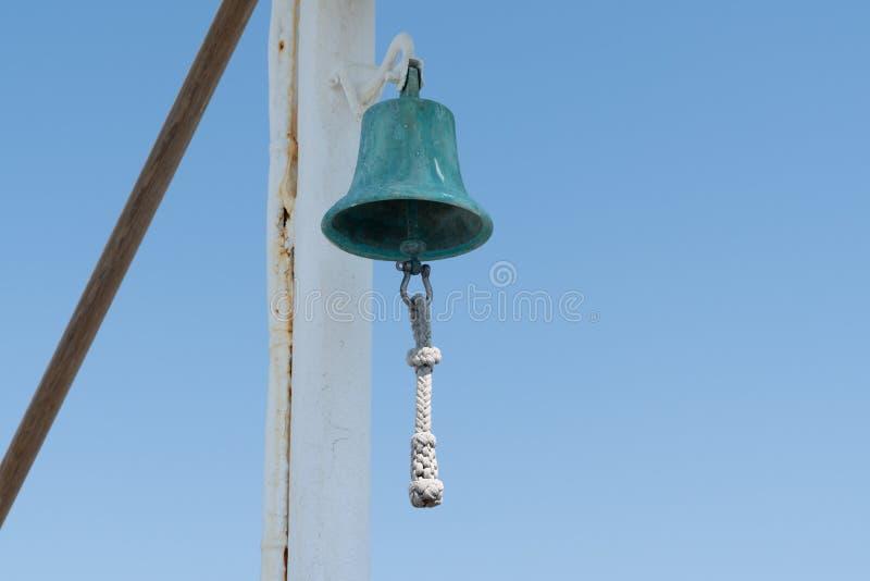 在小船游艇的铜响铃在天空蔚蓝背景 免版税库存图片