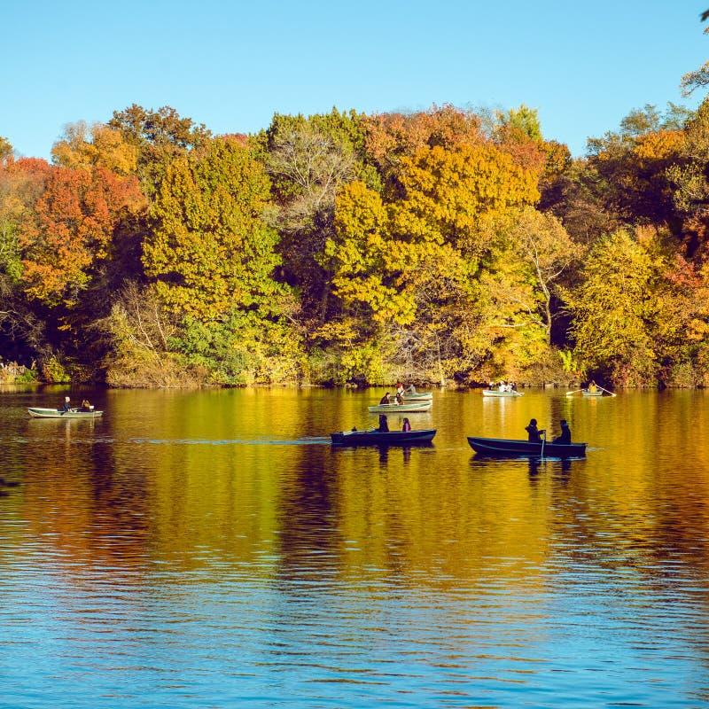 在小船的人salong在湖在秋天季节时间的纽约中央公园 免版税库存图片