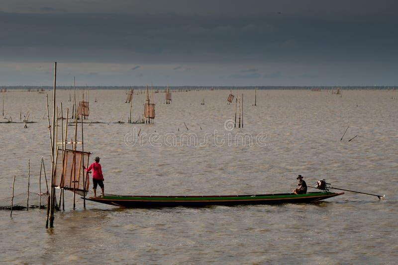 在小船的剪影在湖 免版税库存图片