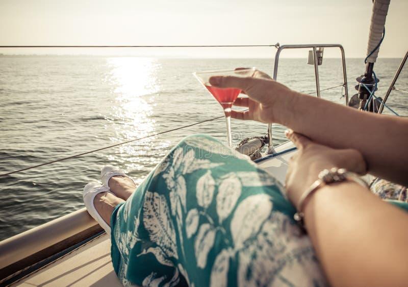 在小船的妇女饮用的鸡尾酒 免版税图库摄影