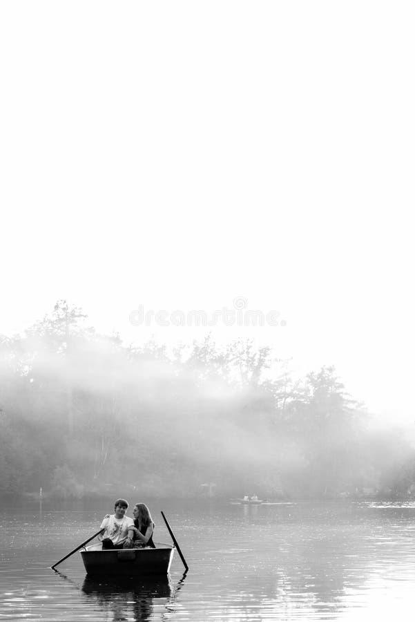 在小船的爱恋的年轻夫妇在有的湖浪漫时间 黑色白色 免版税库存照片