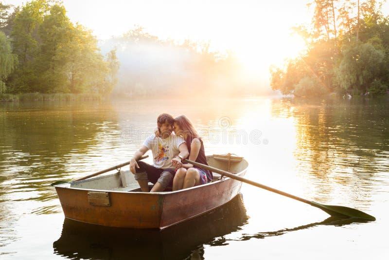 在小船的爱恋的年轻夫妇在有的湖浪漫时间 库存图片
