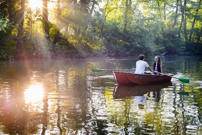 在小船的爱恋的年轻夫妇在有的湖浪漫时间 免版税图库摄影