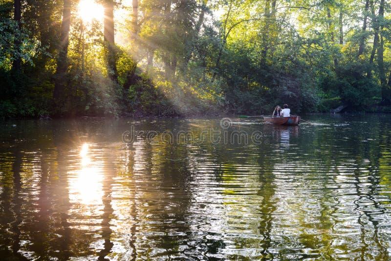 在小船的爱恋的年轻夫妇在有的湖浪漫时间 库存照片