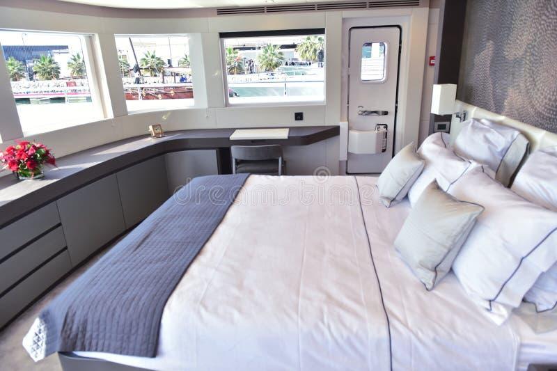 在小船里面的大床有枕头和三个窗口和小门的 免版税库存照片