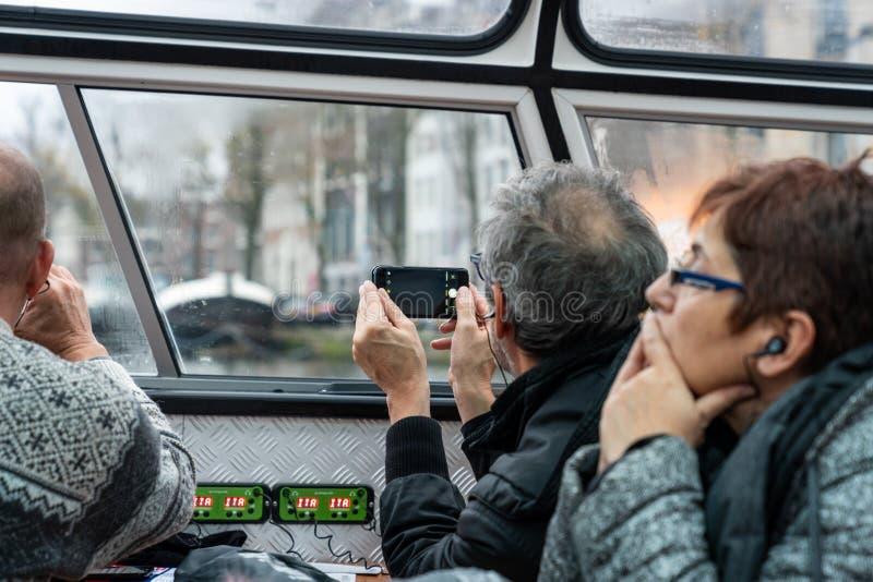 在小船里面看法有游人、两个更老的男人和一名妇女的看在窗口外面的运河巡航小船的 免版税库存图片