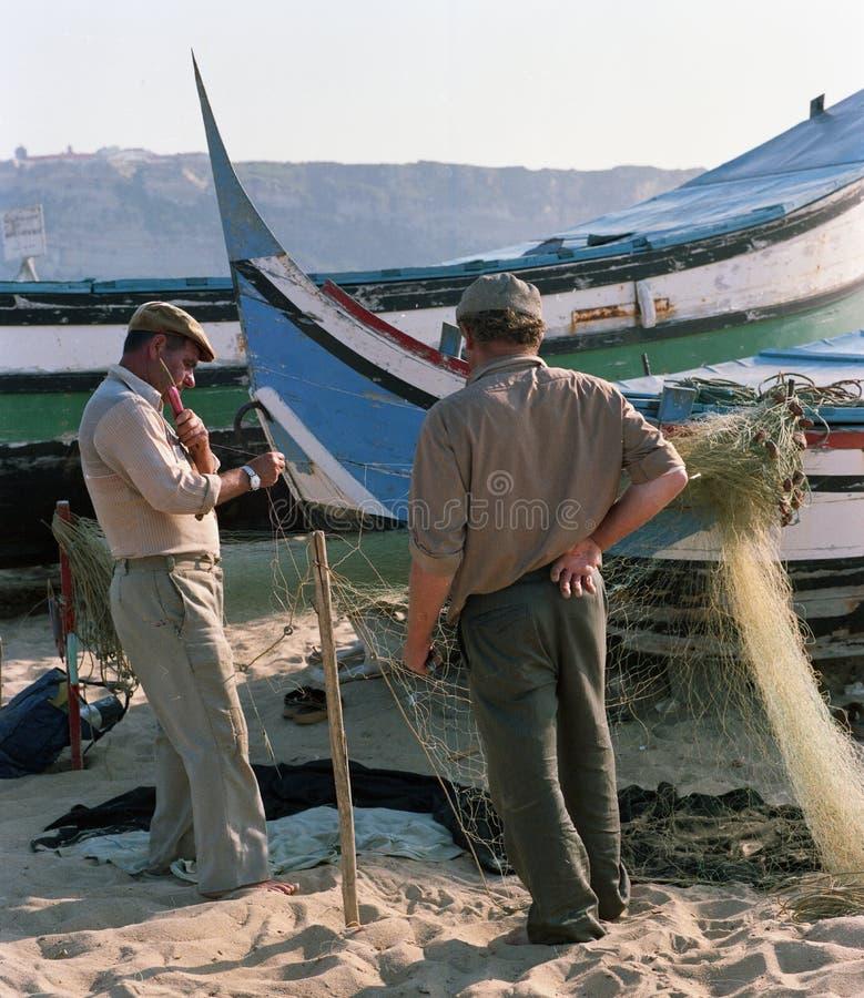 在小船附近的两位渔夫在葡萄牙的一个小村庄20世纪80年代 免版税库存照片