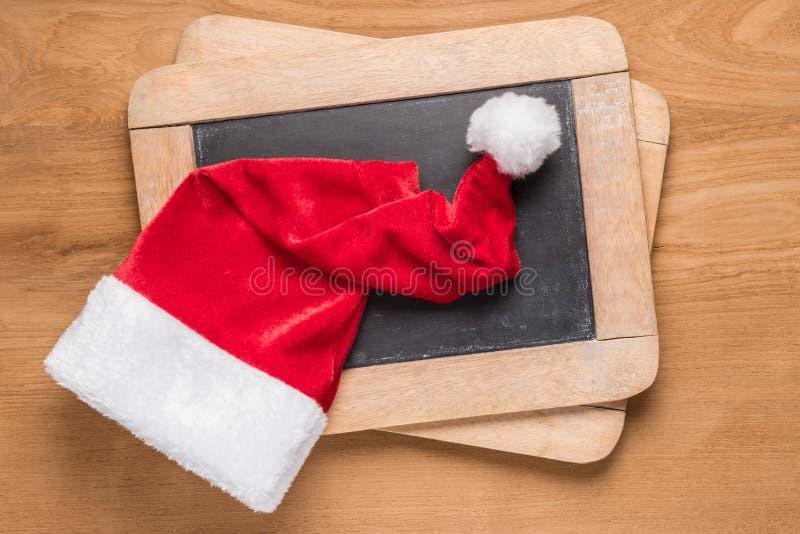 在小黑板的圣诞老人帽子 库存照片