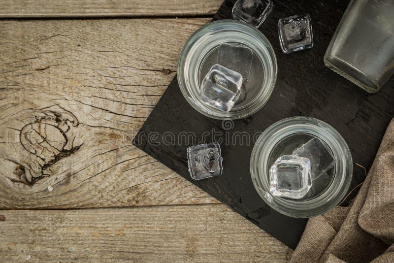 在小玻璃的伏特加酒在土气木背景 免版税库存图片