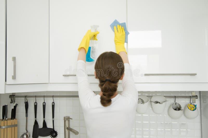 在少妇清洗的白色厨房壁柜的背面图 免版税库存图片