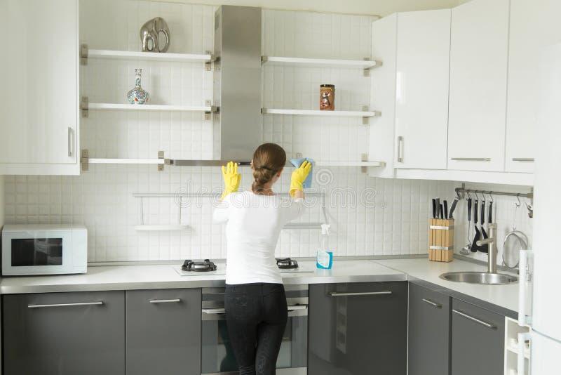 在少妇洗涤的厨房壁橱的背面图 免版税库存图片