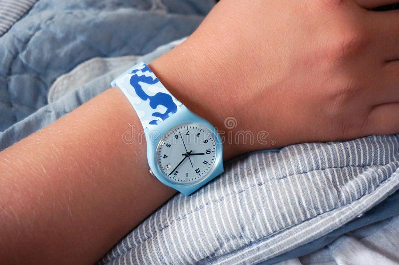 在少年的手上的蓝色Swatch牌手表 免版税库存图片