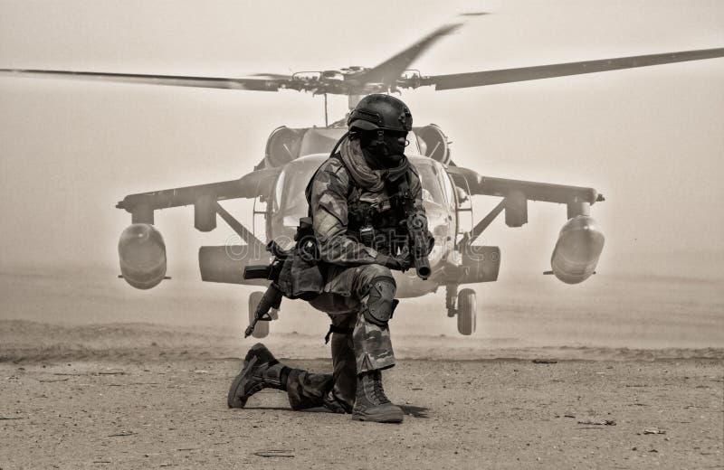 在尘土之间的军事战士在直升机前面 库存图片