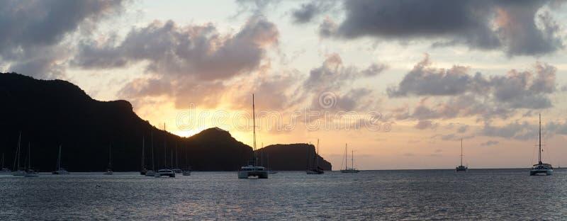 在尤宁岛的日落有帆船游艇的在圣文森特和格林纳丁斯,加勒比附近的多巴哥岩礁 库存照片