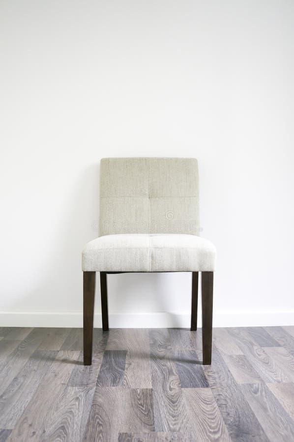 在层压制品的地板上的晚餐椅子 免版税库存照片