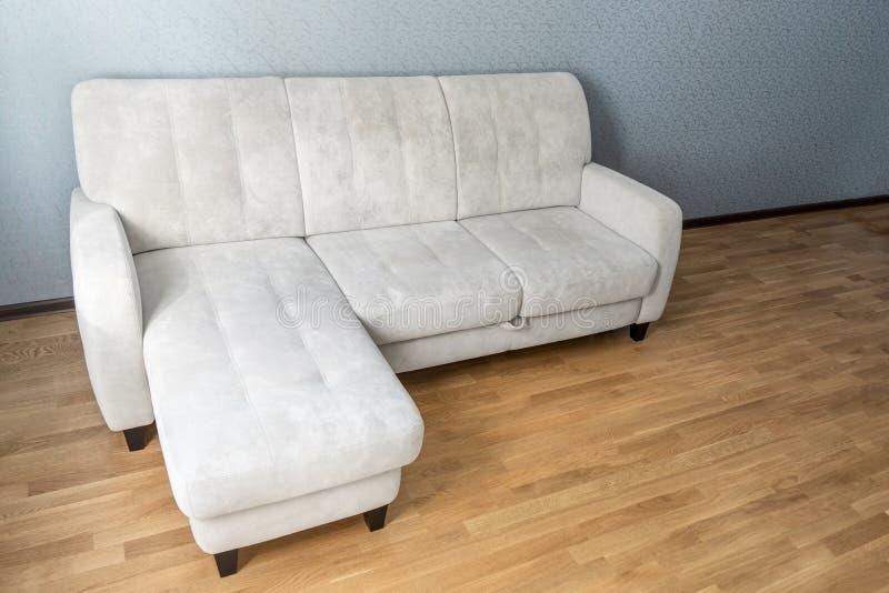 在层压制品的地板上的米黄沙发在空的客厅 免版税库存图片