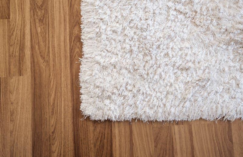在层压制品的木地板上的特写镜头白色地毯在客厅,室内装璜 免版税库存图片