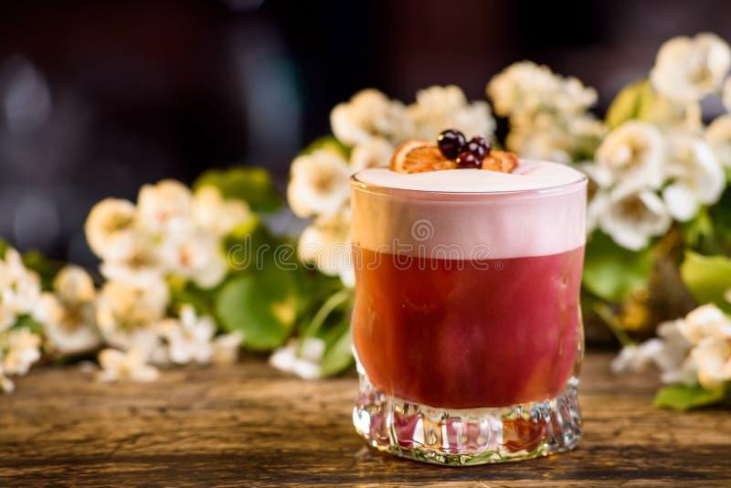 在层数的夏天鸡尾酒,装饰用莓果和橙色切片 在花背景 免版税库存图片