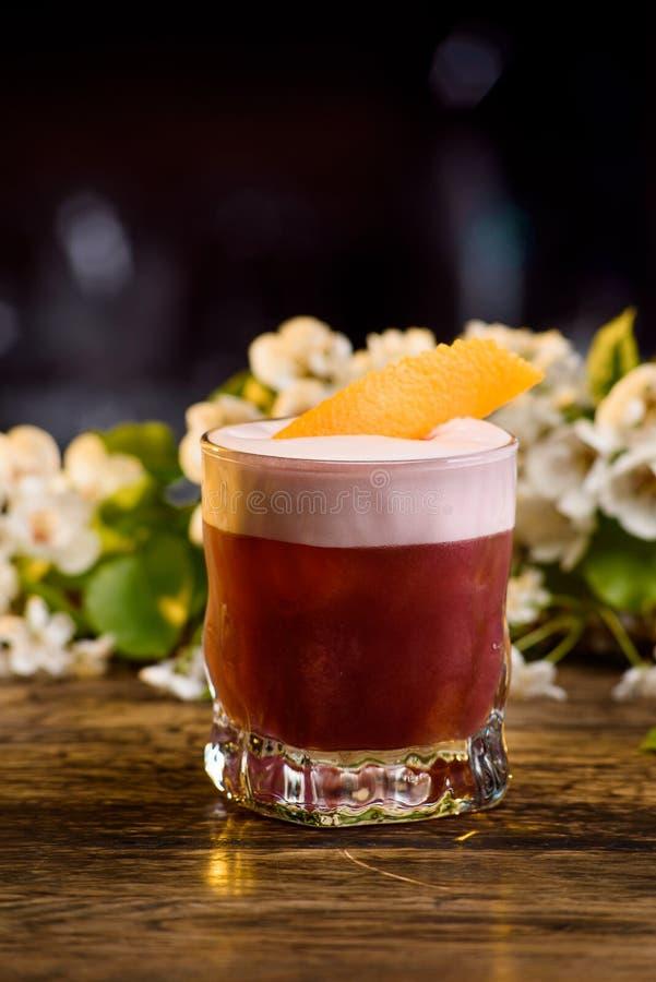 在层数的夏天鸡尾酒,装饰的橙皮 在花背景 免版税库存图片