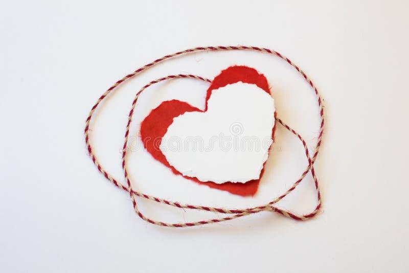 在层状纸华伦泰心脏附近的红色和白色麻线创伤 免版税库存图片