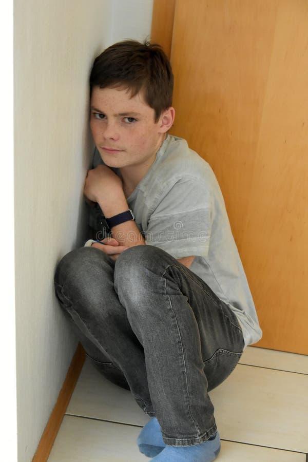 在屋子的角落掩藏的沮丧的男孩 免版税库存图片