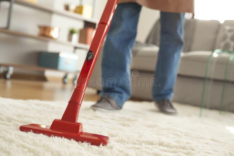在屋子里供以人员有吸尘器的清洁地毯 免版税图库摄影