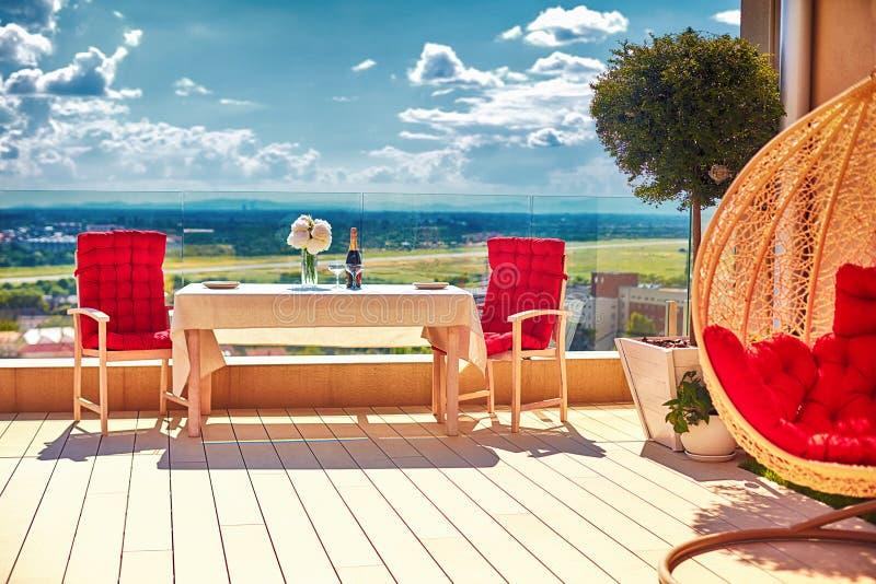 在屋顶上面露台的放松的用装备的区域温暖的夏日 免版税图库摄影