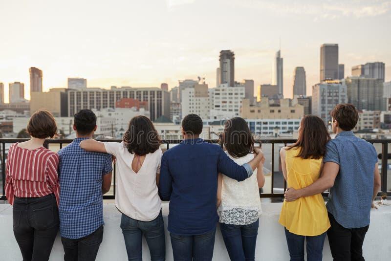 在屋顶大阳台会集的朋友背面图看在城市地平线 免版税库存照片