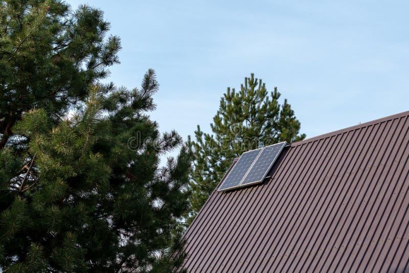 在屋顶安装的太阳电池板在绿色树背景的一栋乡间别墅  r 库存图片