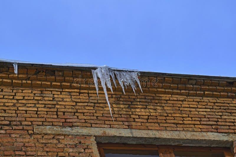 在屋顶峰顶的冰柱 库存照片