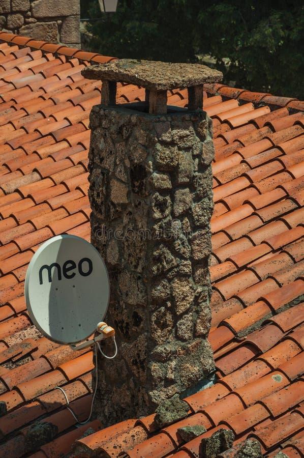 在屋顶的一个石烟囱困住的抛物面天线 免版税库存图片
