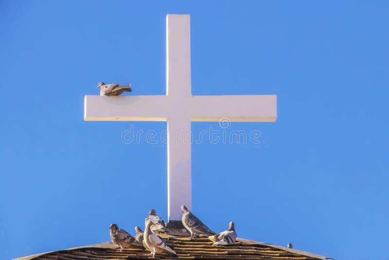 在屋顶的木十字架反对与栖息对此的鸽子的天空蔚蓝以下-特写镜头 库存图片
