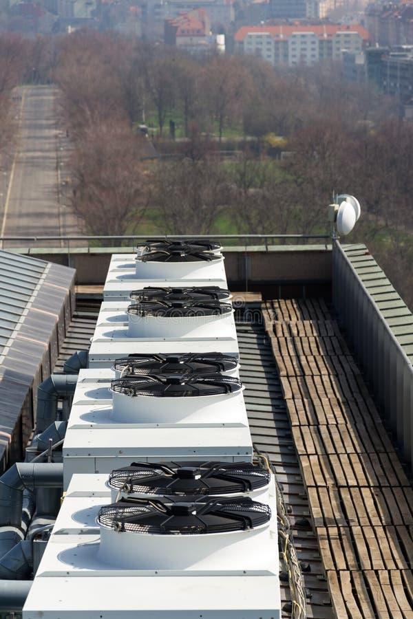 在屋顶的空调通风设备有房子的在背景中 免版税图库摄影