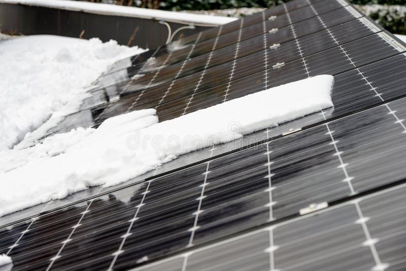 在屋顶盖子的光致电压的盘区有雪的,在冬天 图库摄影