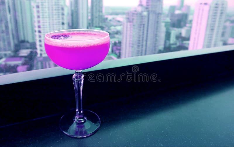 在屋顶酒吧的桌上的鲜粉红色色的鸡尾酒有在背景的摩天大楼视图 免版税库存图片