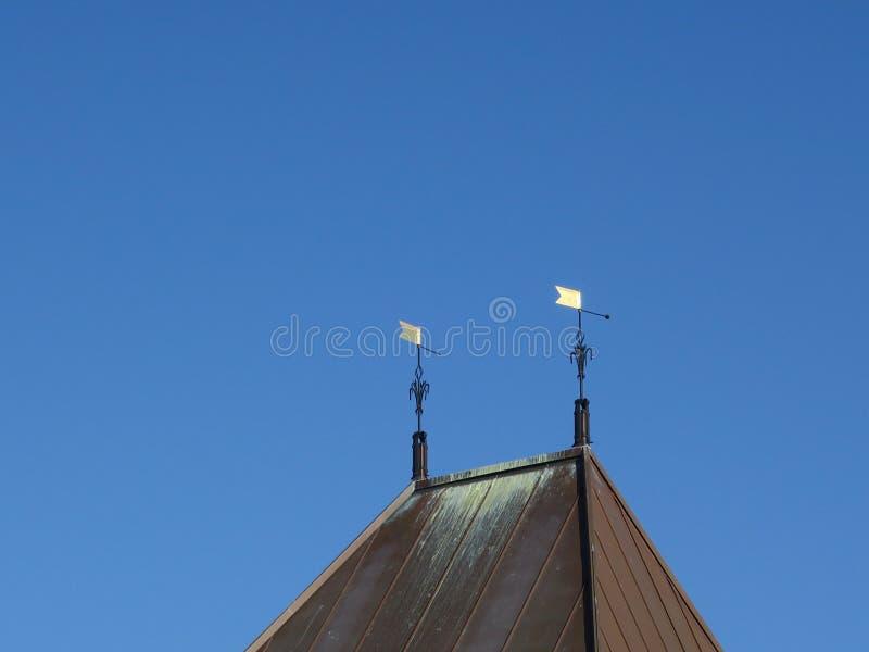 在屋顶顶部的两面金黄旗子 库存图片