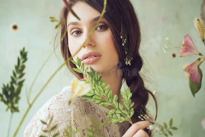 在屏幕后的妇女有干花和植物的 库存照片