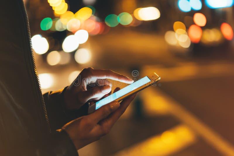在屏幕智能手机的女孩短信的手指在背景照明焕发bokeh光在夜大气城市,使用在f的行家 免版税库存图片