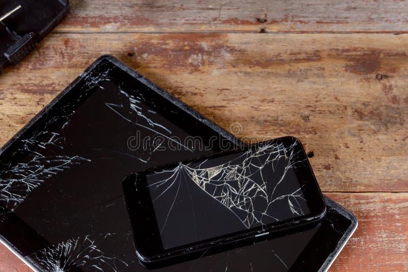 在屏幕电子设备木头背景的残破的玻璃屏幕 库存照片