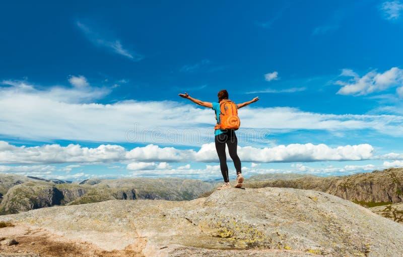 在山、刺激和启发的妇女成功的远足的剪影在日落 免版税图库摄影