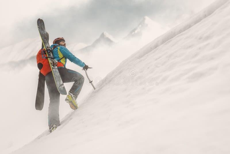 在山、年轻人和极端冬季体育顶部的滑雪者 免版税库存图片