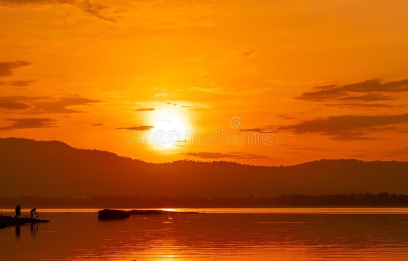 在山上的美丽的日出天空在水库 人们钓鱼与在河的一根钓鱼竿 水库风景  库存照片