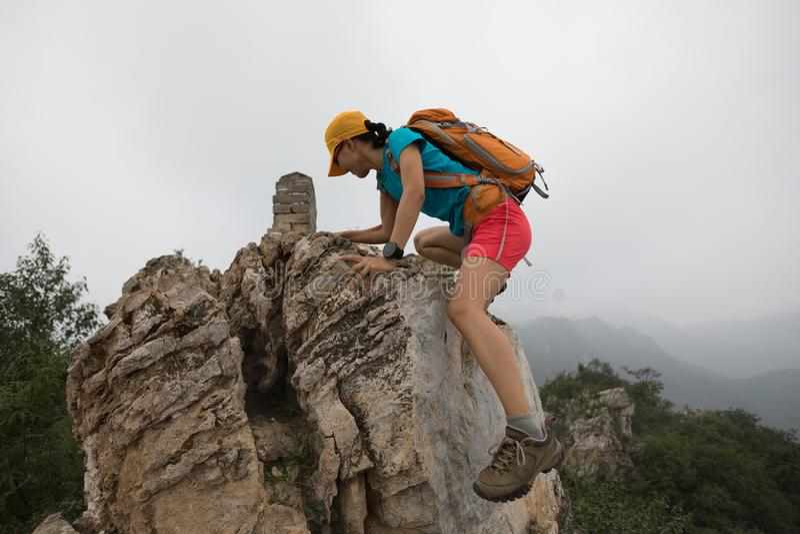 在山上面的妇女登山人上升的岩石  库存照片
