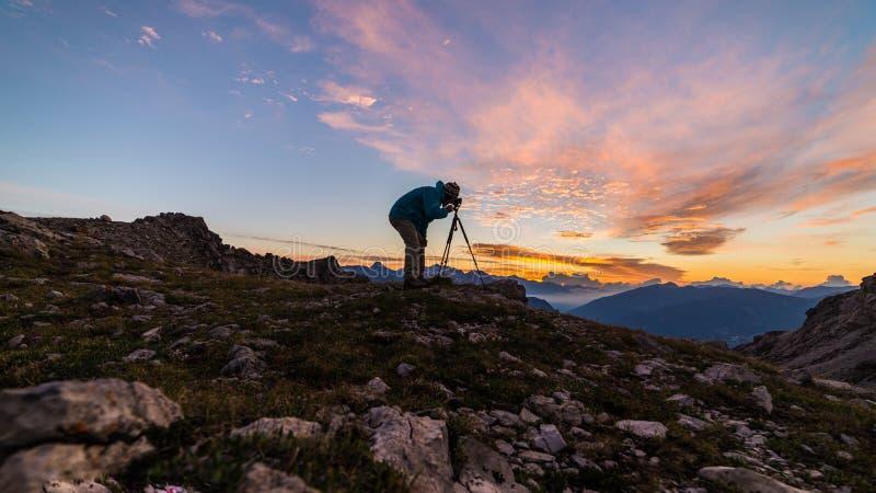 在山上面的摄影师与在三脚架的照相机在日出光五颜六色的天空scenis环境美化,征服成功领导conce 库存照片