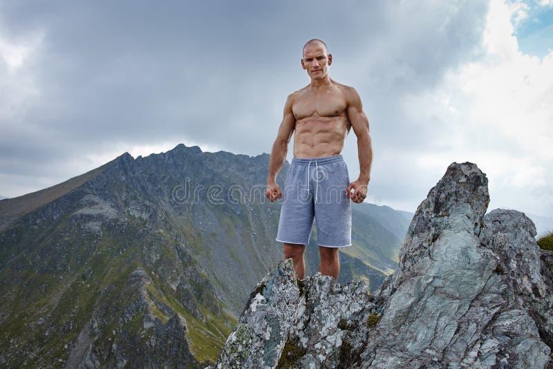 在山上面的赤裸上身的运动人 免版税库存照片