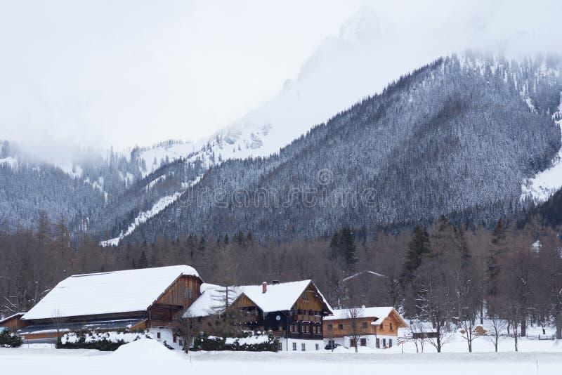 在山下的冬天村庄 免版税库存照片