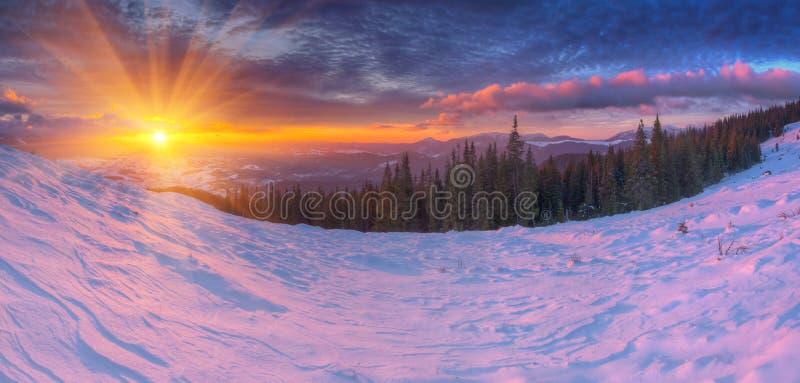 在山与色的云彩和桃红色雪的惊人的五颜六色的日出在前景 与雪的剧烈的冬天场面 库存图片