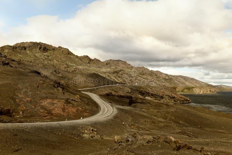 在山中的弯曲道路在湖 剧烈的天气 冰岛 免版税库存图片