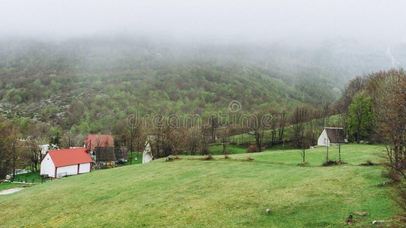 在山之间的小镇 ?? ? 薄雾烟雾 黑山村庄房子和绿色风景 库存图片